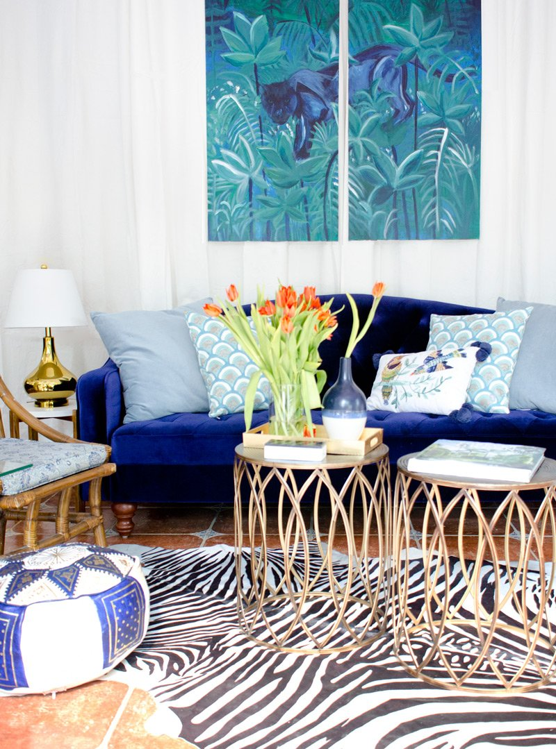 Eclectic living room with blue velvet sofa, zebra rug, and bronze bunching tables.