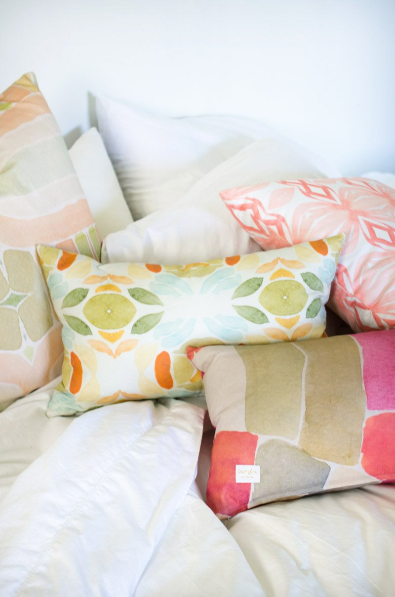 White bedroom with splashes of colorful watercolor patterns from bunglo's pillow collection.