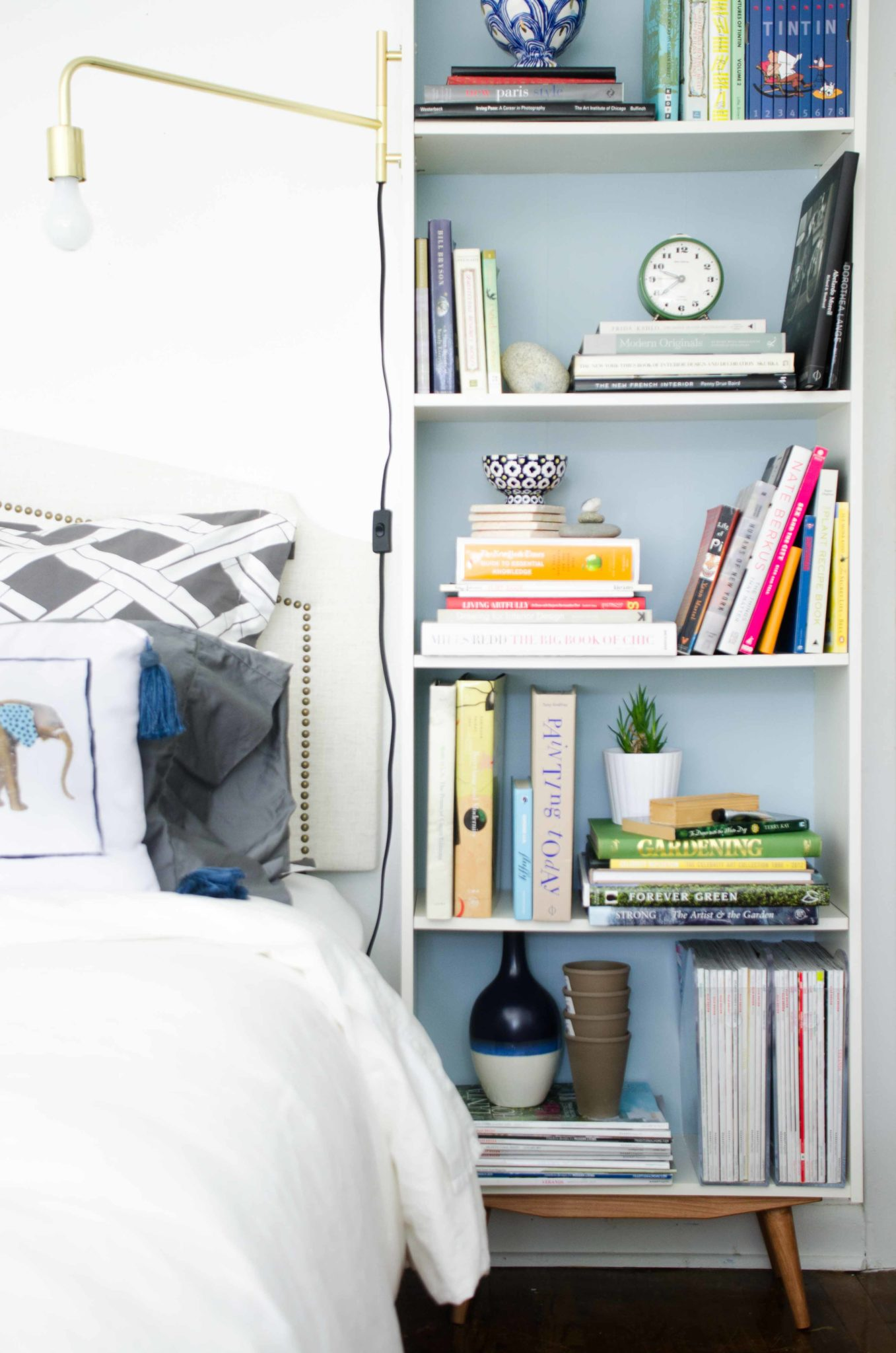 Mid century bookcase with brass swing arm sconce in a modern bedroom