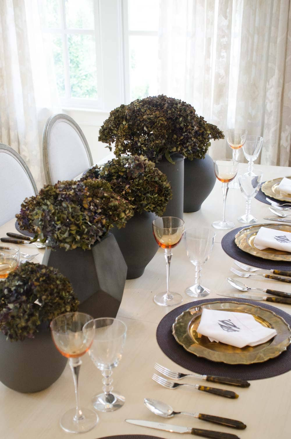 Black hydrangeas line a pale dining room table
