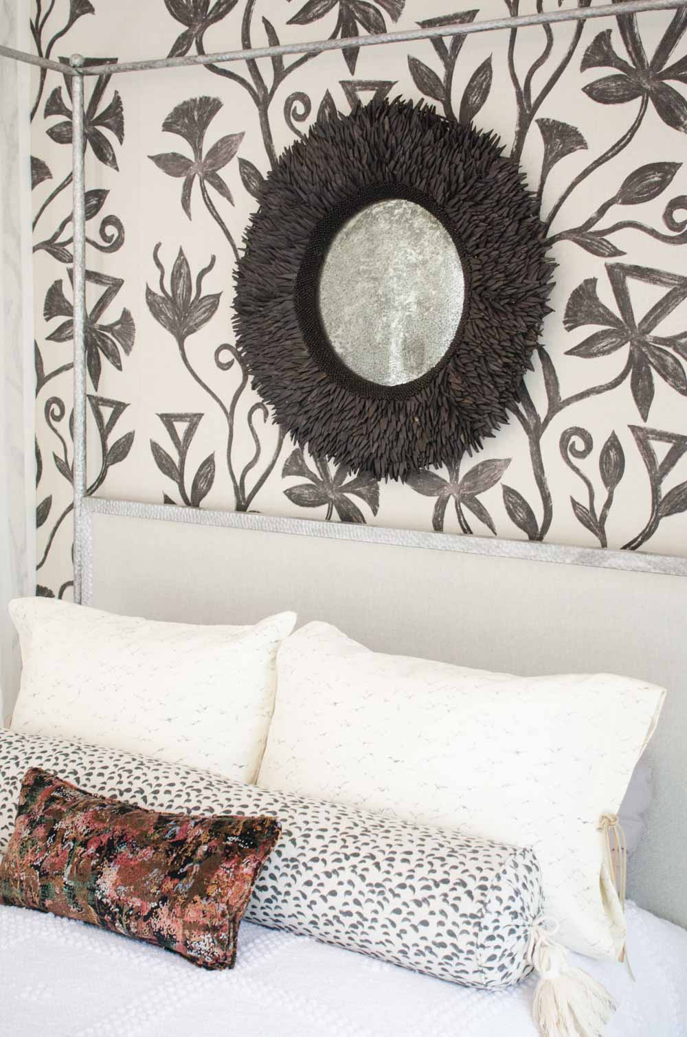 Eclectic bedroom with painted floral wallpaper and black wood mirror above bed