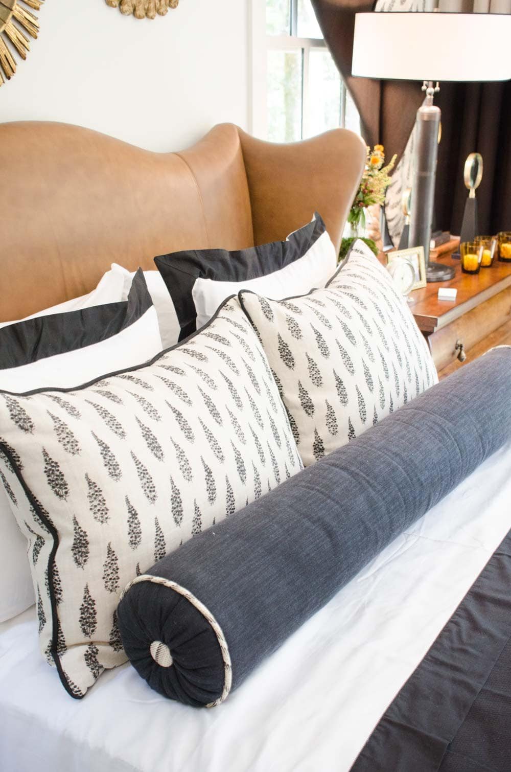 Handsome bed with leather headboard and charcoal lumbar pillow