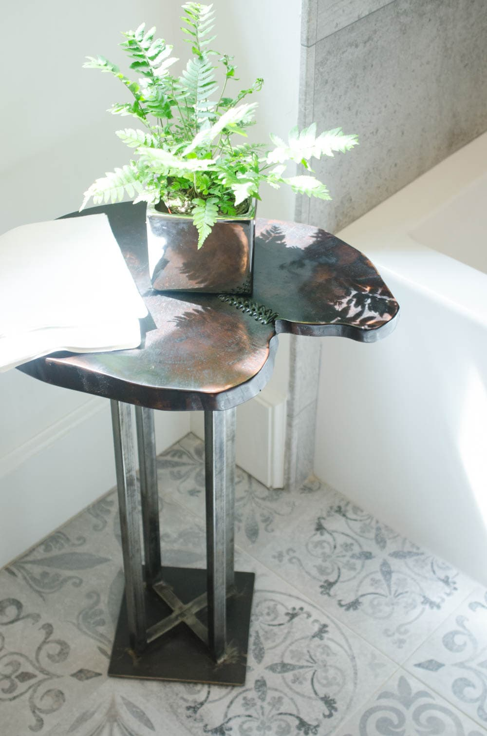 Bathroom vignette with raw wood table and porcelain floors