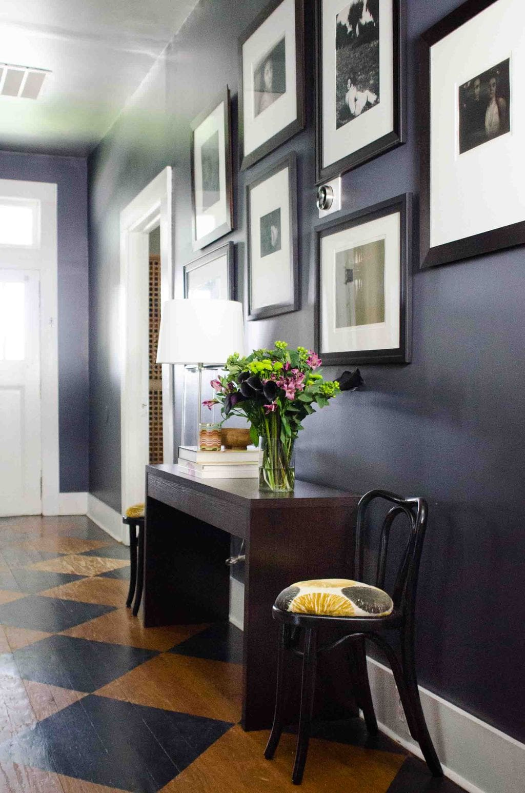 Moody charcoal entry hallway with black and white gallery wall