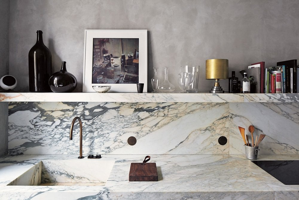 Sleek veined marble and a floating shelf above the kitchen sink.