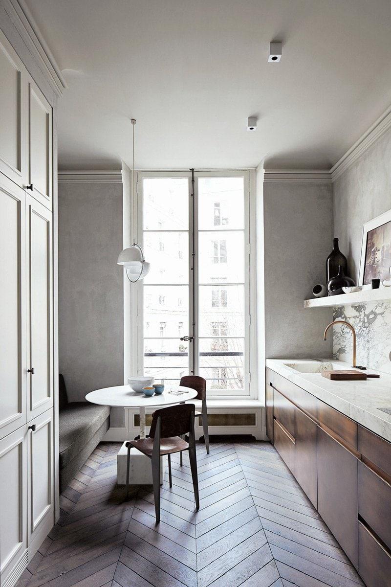 The modern kitchen with parquet floor in a Paris apartment.