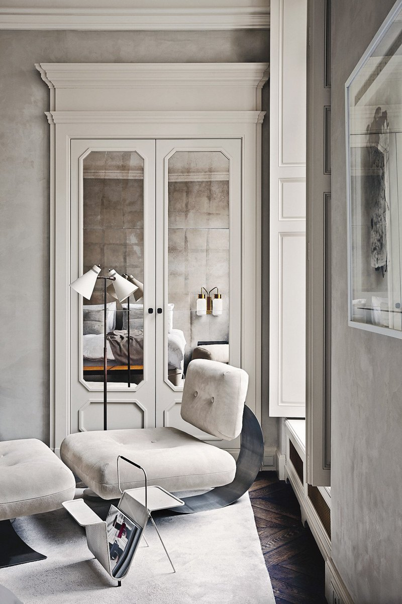 A luxurious, gray bedroom with textured walls and mirrored doors.