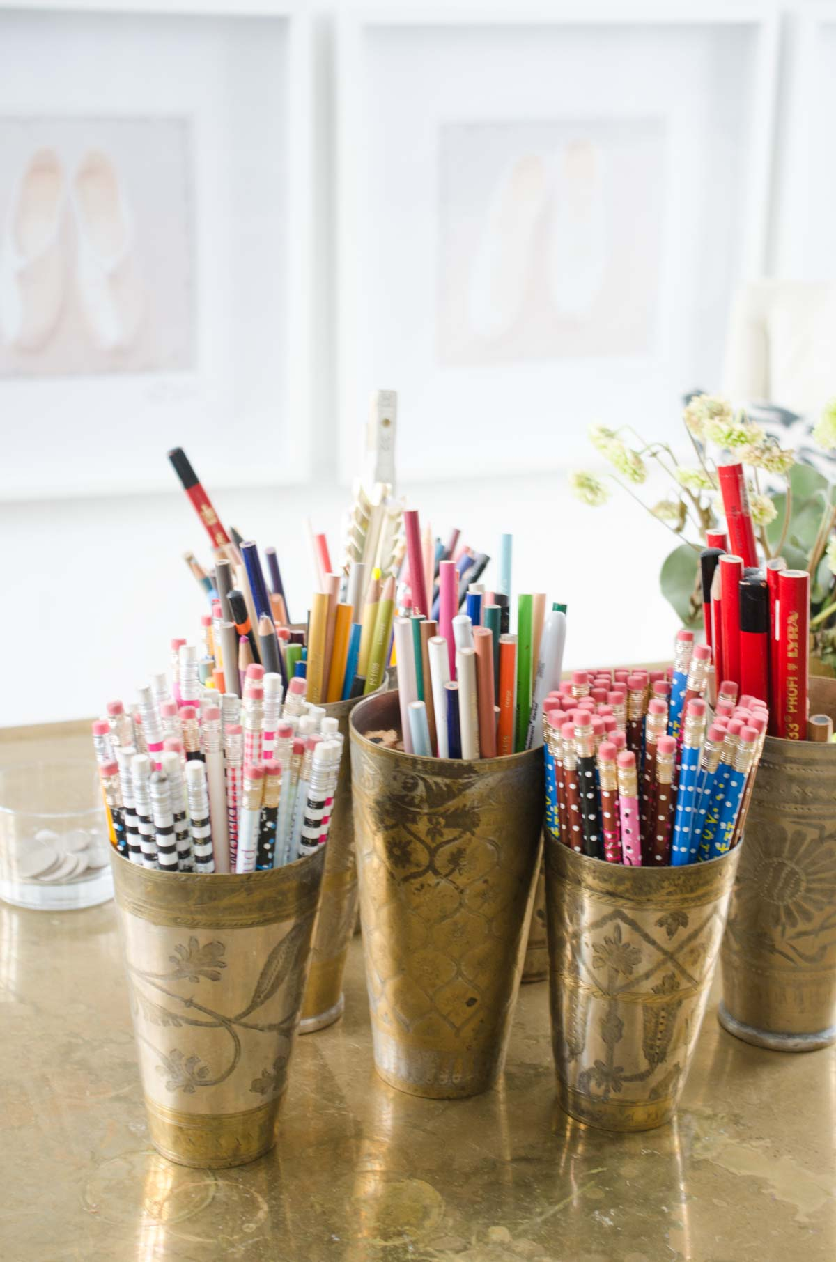 Brass desk with cups of pens and pencils on @thouswellblog