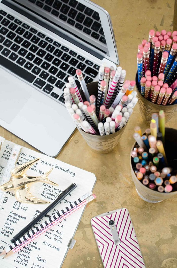 Brass desk with cups of pens and pencils and Jonathan Adler Moto X on @thouswellblog