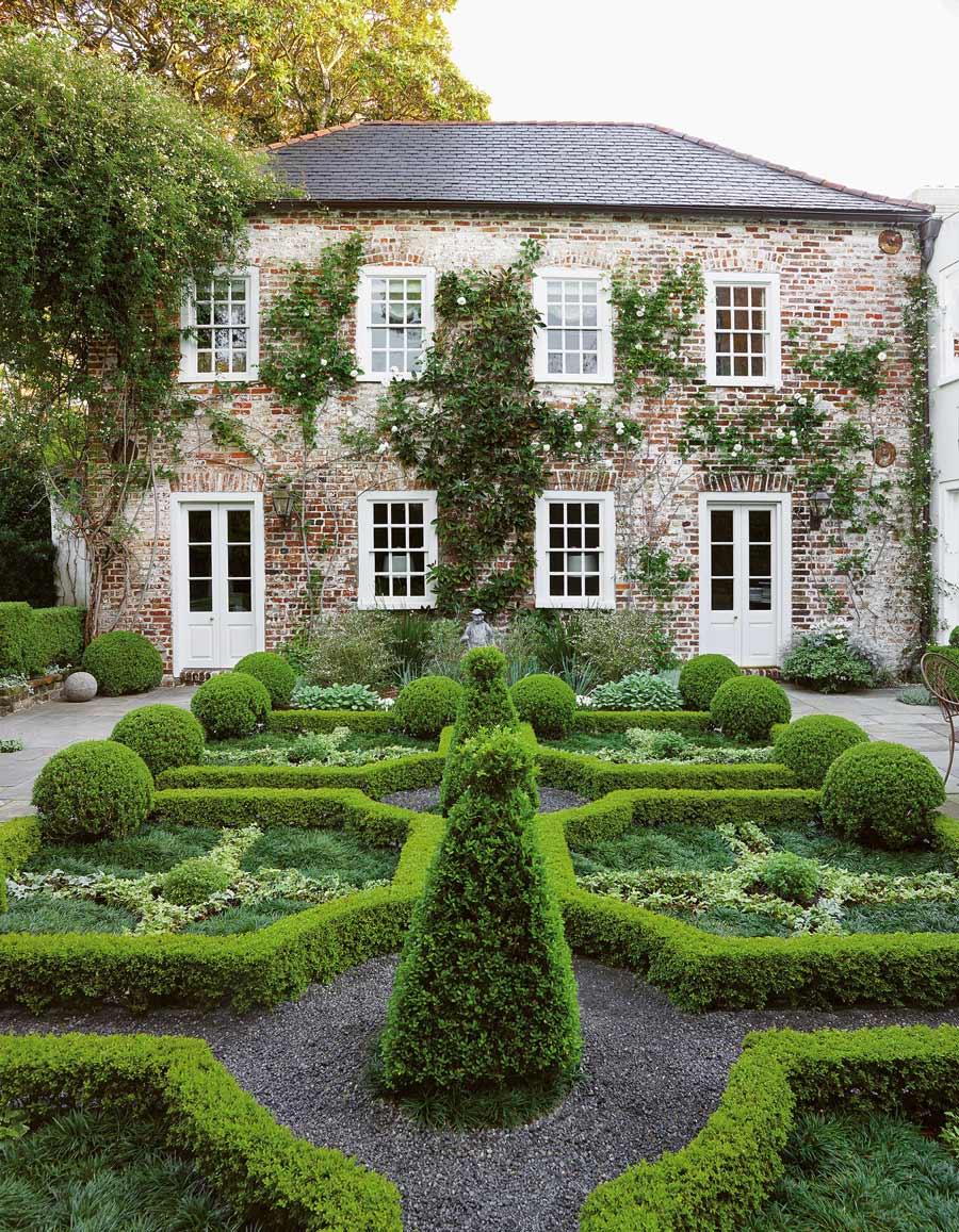 South Carolina home with a boxwood hedge pattern and climbing magnolia via @thouswellblog