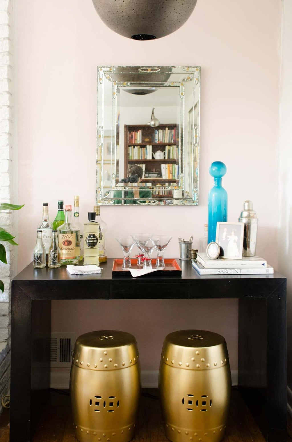 Bar with black parsons table and pink accent wall via @thouswellblog