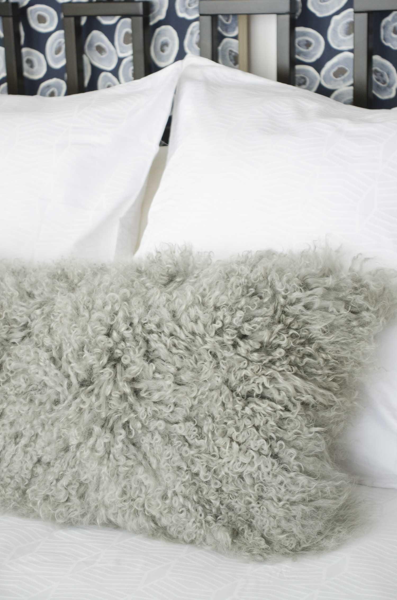 Furry Mongolian lamb lumbar pillow on the bed on @thouswellblog