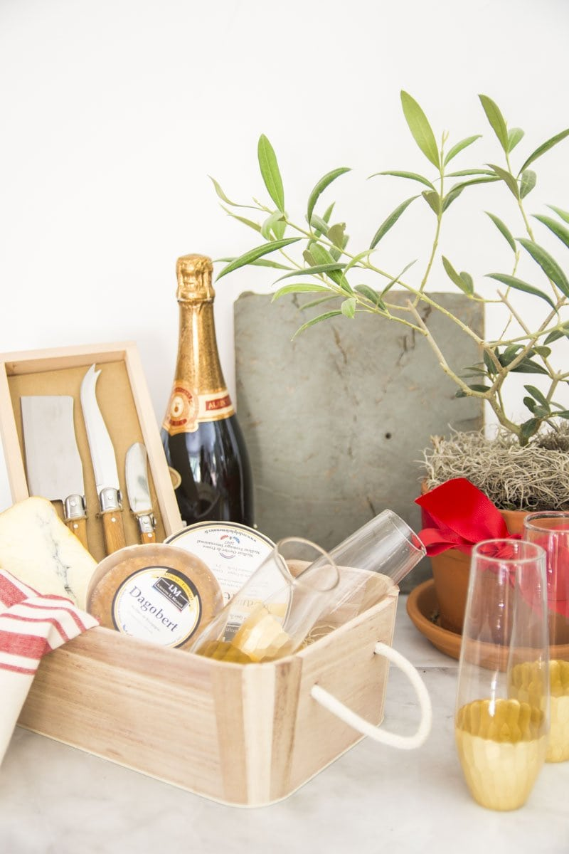 Gift basket with cheese, knives, tea towel, and champagne flutes from World Market on Thou Swell