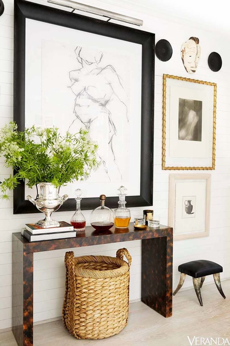 Burl console table with eclectic art and wicker basket on Thou Swell @thouswellblog