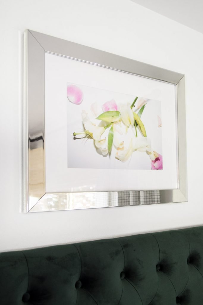 Mirrored frame from Framebridge above green tufted headboard on Thou Swell @thouswellblog