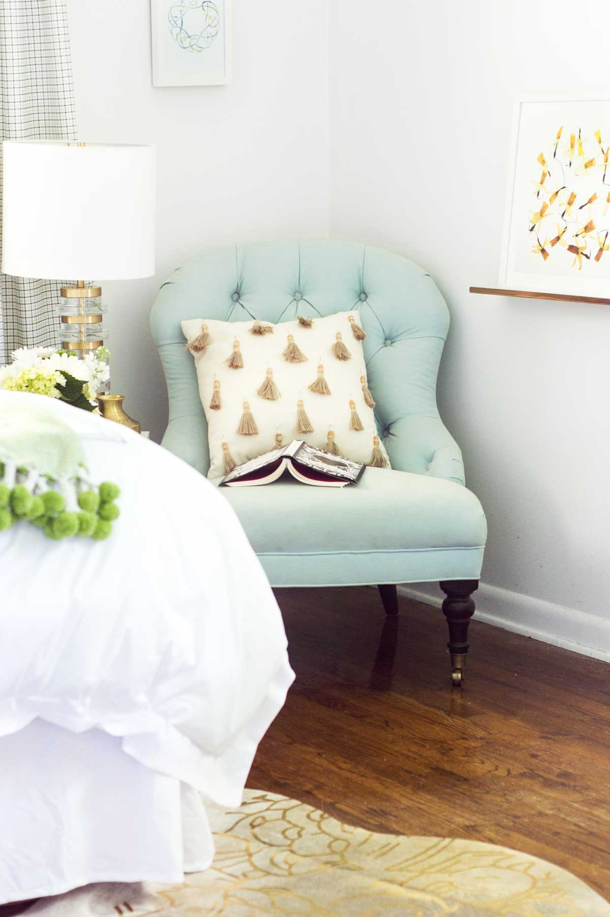 Blue tufted slipper chair with tassel pillow and brass table lamp on Thou Swell @thouswellblog