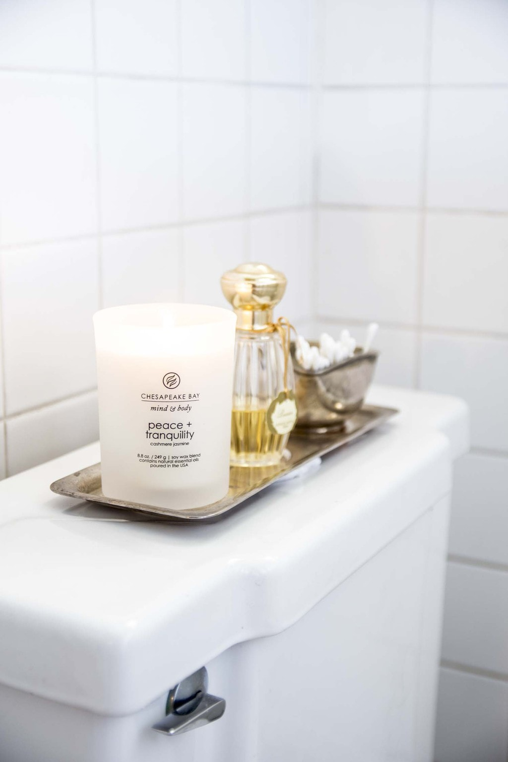 Peace & Tranquility scented candle in white bathroom with silver tray and perfume on Thou Swell @thouswellblog