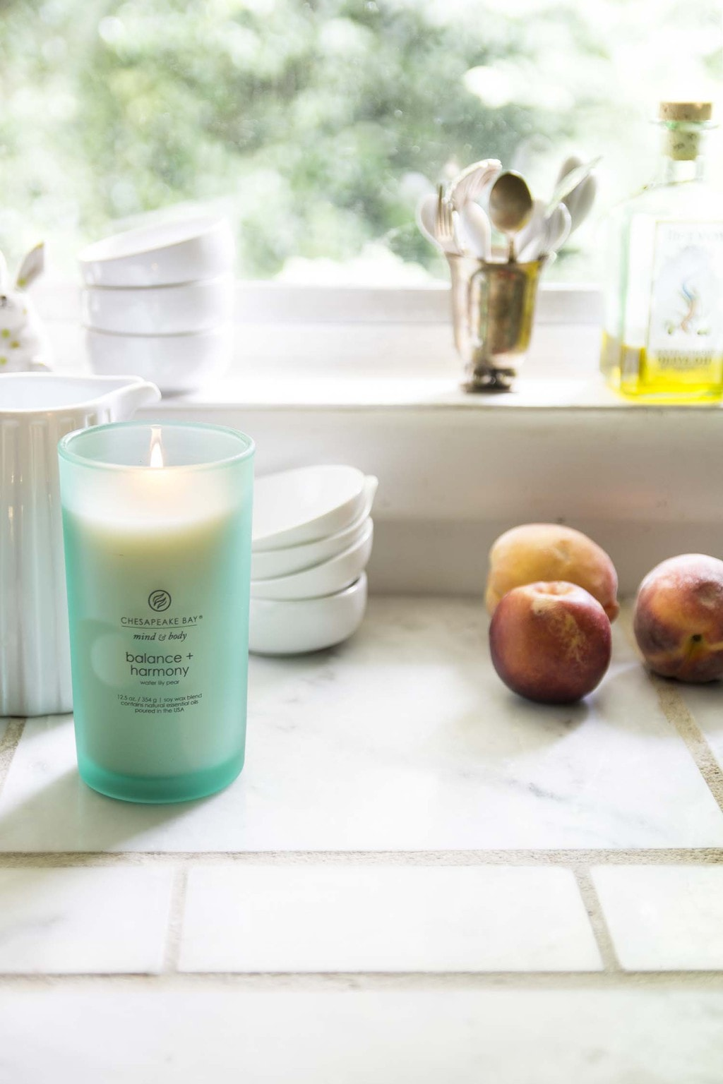 Chesapeake Bay Candle in the kitchen with white dishware and peaches on Thou Swell @thouswellblog