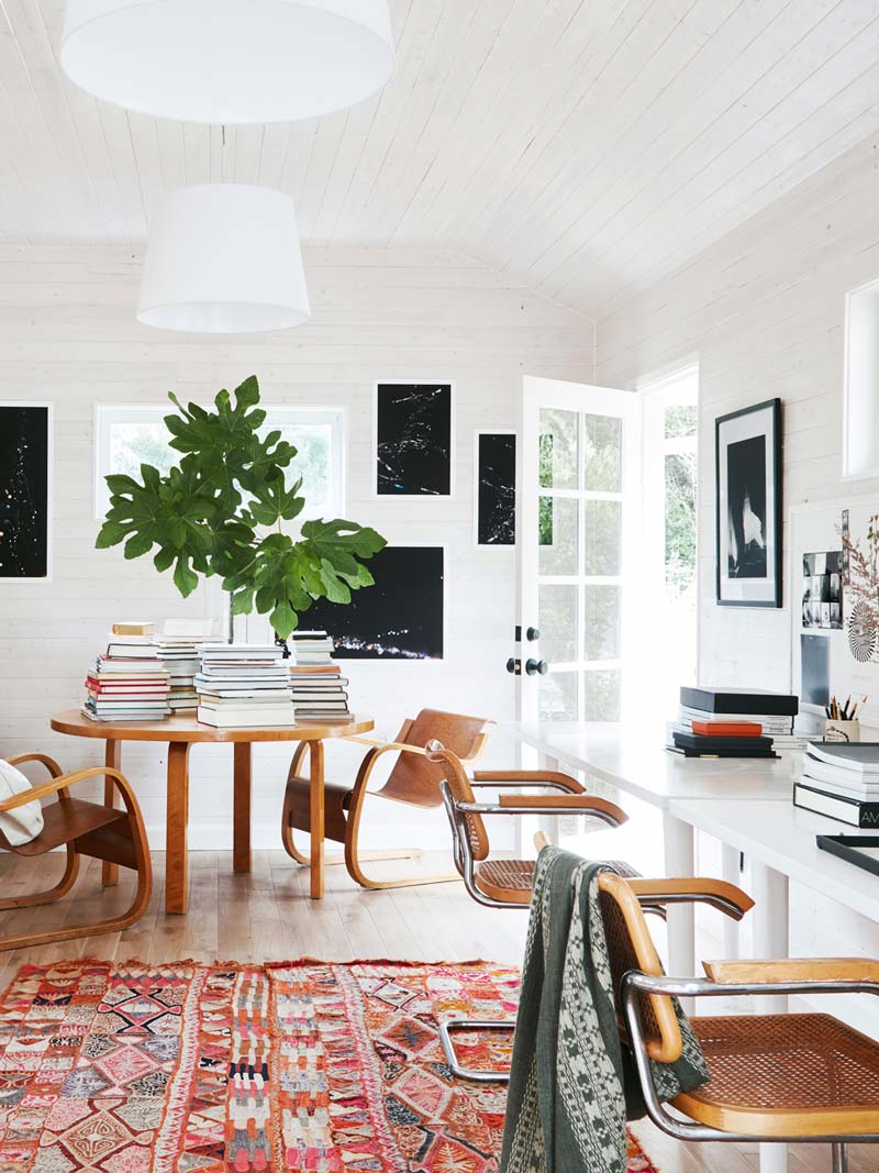 Bright and colorful home office workspace with entry table piled with books and white washed