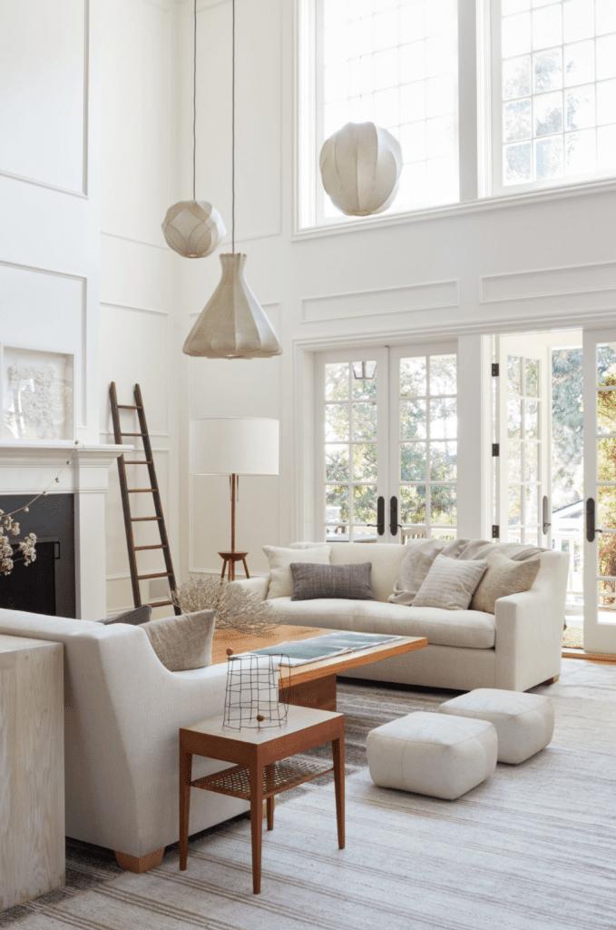 Serene cream living room with all-white upholstery and pendant lights on Thou Swell @thouswellblog