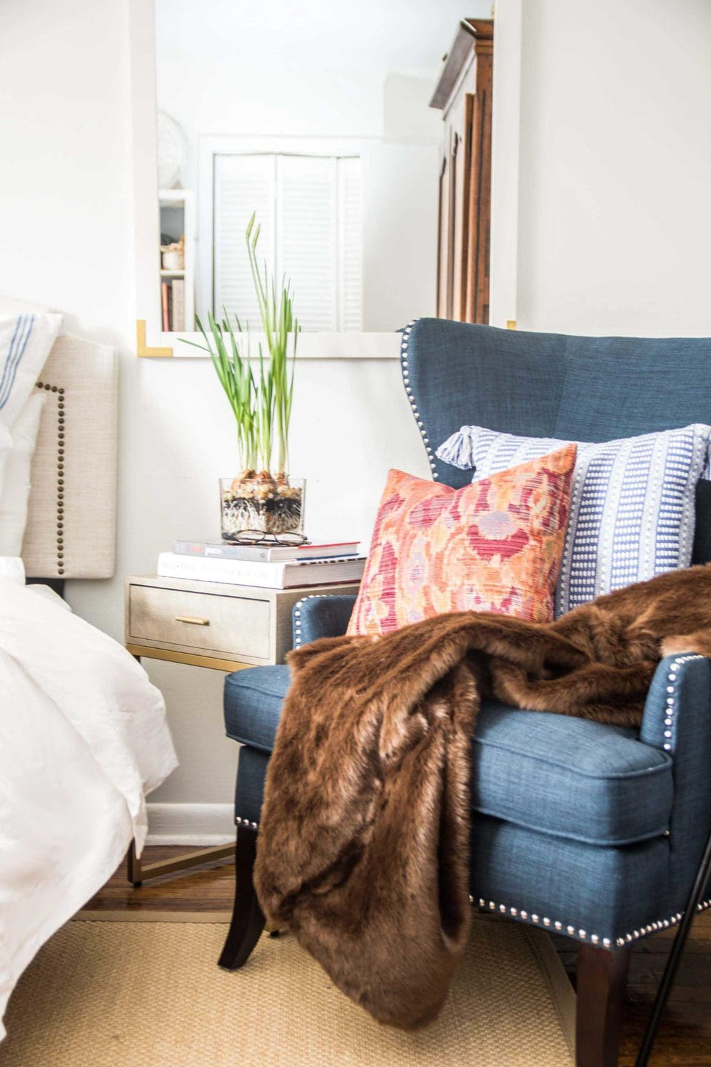 I filled the chair with a brown faux fur throw seriously the best faux ive ever felt and a cozy ikat pillow to add the perfect pop of red to the
