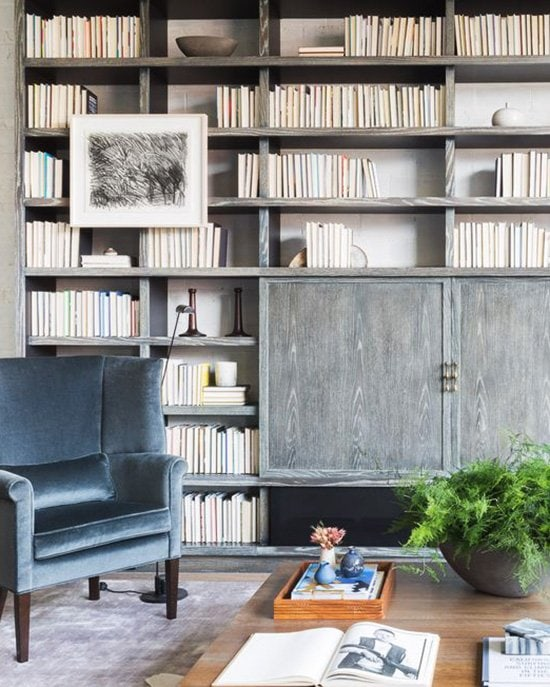 Urban loft with floor-to-ceiling bookcase and velvet wingback chair on Thou Swell @thouswellblog