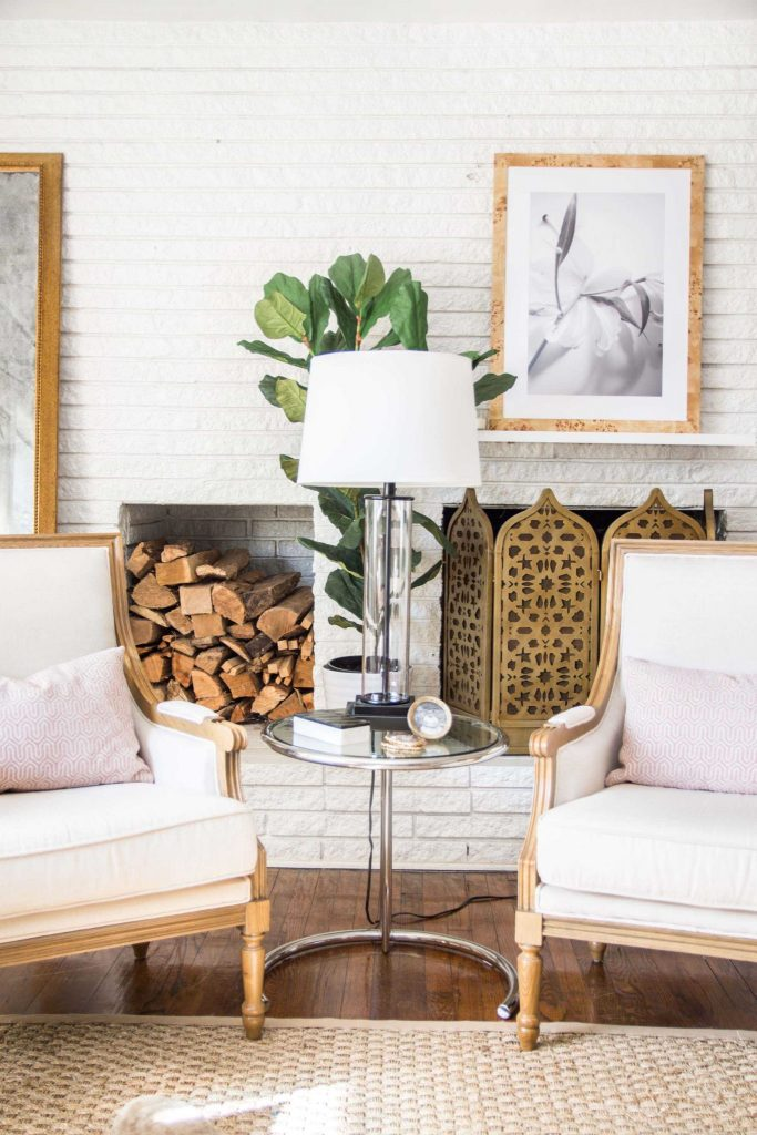 White brick fireplace with gold fireplace screen, stacked logs, linen armchairs, and pink pillows on Thou Swell #livingroom #livingroomdesign #homedecor #homedesign #interiordesign #pinkdecor #blush