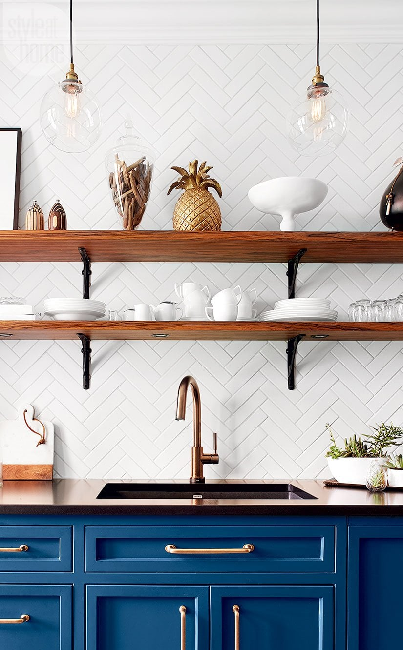 Pineapple decor in a french kitchen with blue cabinets and open shelving on thou swell