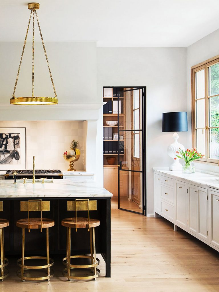 Beautiful modern kitchen with brass counter stools