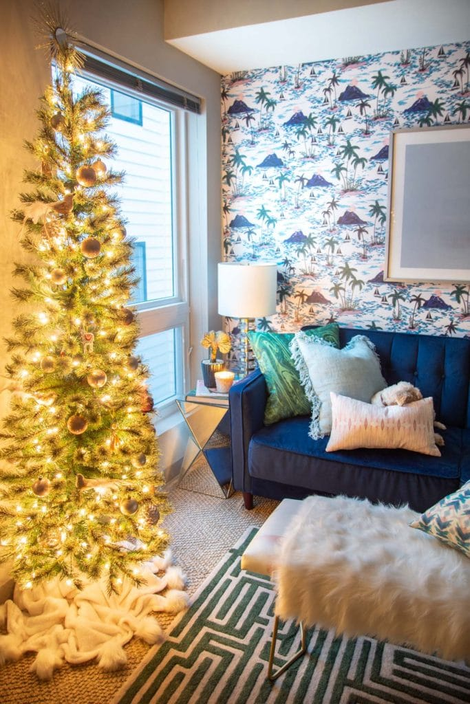 Playful apartment Christmas tree with whimsical blush ornaments and bird decorations in a tropical living room