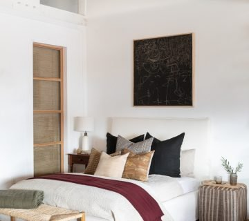 California bedroom design with black painting above bed and vintage kilim textiles and pouf designed by Amber Interiors on Thou Swell #bedroom #bedroomdesign #bedroomdecor #homedecor #homedecorideas #interiordesign