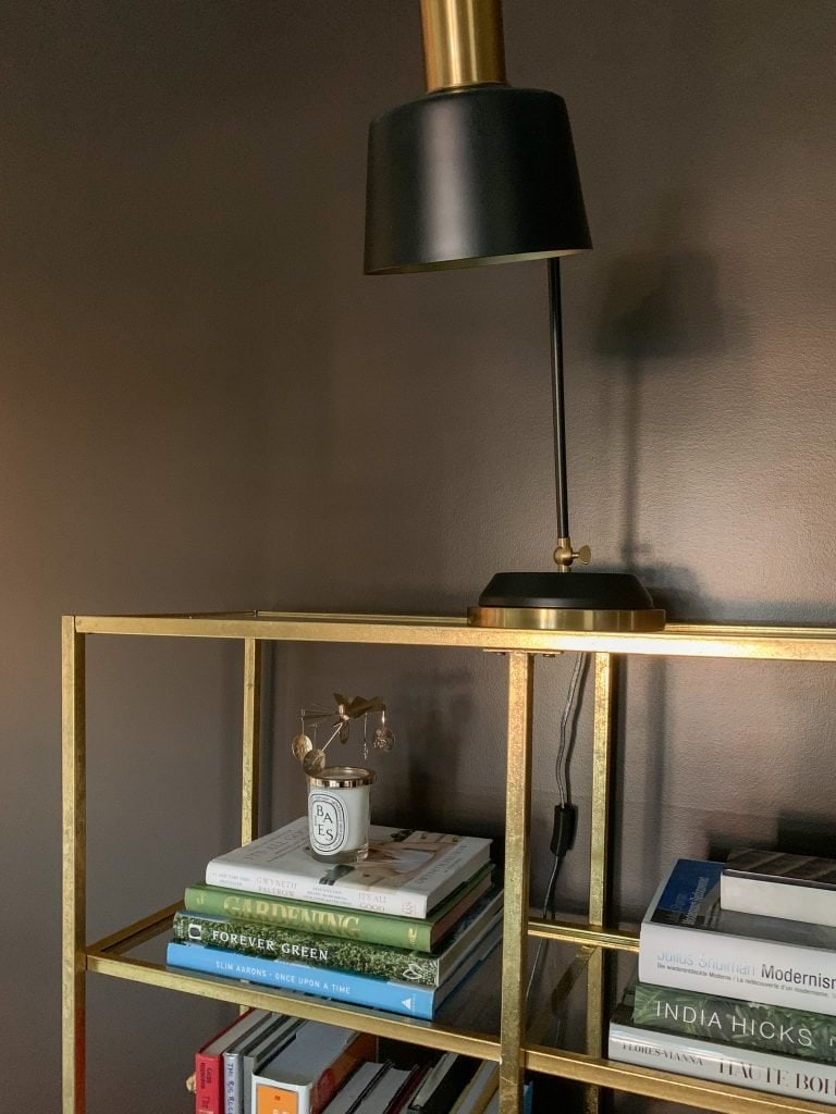 Brown study living room design with gold bookcase, black lamp, and brown walls on Thou Swell #study #livingroom #bookcase #tasklamp #blacklamp #goldbookcase #brownwalls