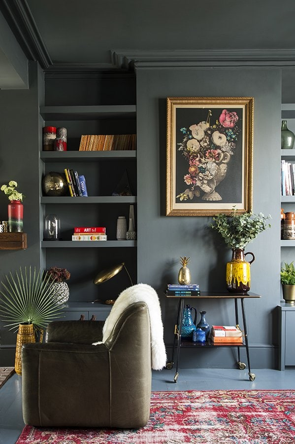 Dark green living room walls with pops of color, eclectic home decor, living room design on Thou Swell #livingroom #livingroomdesign #livingroomdecor #greenlivingroom #darkgreen #darkgreenwalls #greenwalls