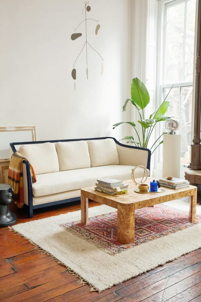 Pied-a-terre furniture collection by Urban Outfitters home with cream and black frame sofa with burl coffee table on Thou Swell